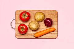 Two Fresh Tomatoes Near Potatoes, Violet Onion And Carrot. Healthy Eating. Two Fresh Tomatoes Near Potatoes, Violet Onion And Carrot On A Wooden Chopping Board Royalty Free Stock Image