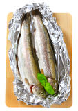 Two fresh trout on tin foil Stock Photo