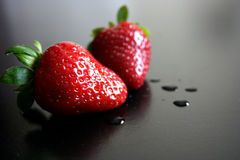 Two fresh wet strawberries. Two fresh and wet strawberries on a dark background stock photo