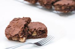 Two freshly baked brownies with fork on white. Two freshly baked brownie pieces on white with a fork and rack of extra brownies in the background Stock Photos