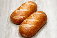 Two freshly baked loaves on a light wooden background.  stock photo