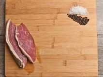 Two freshly sliced steaks on a bamboo cutting board with piles of sea salt and pepper corns Royalty Free Stock Photography