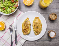 Two fried chicken breasts with curry, fresh orange juice, fresh salad nutrition athletes wooden rustic background top view Royalty Free Stock Image