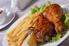 Two fried chicken drumsticks with french fries Royalty Free Stock Image