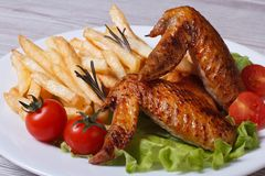Two fried chicken wings, french fries, tomato and lettuce Royalty Free Stock Photography