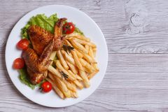 Two fried chicken wings, french fries. top view. Two fried chicken wings, french fries, tomato and lettuce on a plate. top view Royalty Free Stock Photos