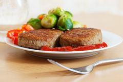 Two fried cutlets with vegetables Stock Images