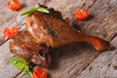 Two fried duck legs and basil, cherry tomatoes closeup on table Stock Image