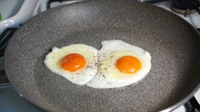 Two fried egg yolks fried in a stone pan. On a gas stove stock footage