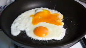 Two fried egg yolks fried in stone pan. Two fried egg yolks fried in a stone pan on a gas stove stock video footage