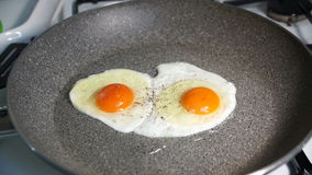 Two fried egg yolks fried in a stone pan. On a gas stove stock video footage