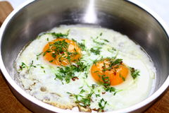 Two fried eggs. Bruzzeln without any hurry in a metal frying pan. Cress as a decoration on top Stock Photography
