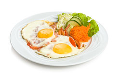 Two fried eggs. With a vegetable side dish. Isolated on white. Isolated by clipping path Stock Photos