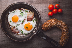 Two fried eggs with bacon and onion, tomato and bread on the side. Shot on a wooden table Stock Photo
