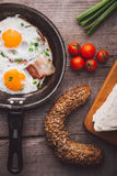 Two fried eggs with bacon and onion, tomato and bread on the side. Shot on a wooden table Royalty Free Stock Photo