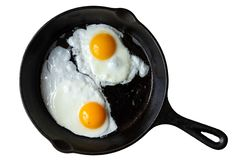 Two fried eggs in cast iron frying pan isolated on white from ab stock photo