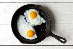 Two fried eggs in cast iron frying pan isolated on white painted stock photo