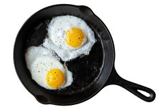 Two fried eggs in cast iron frying pan sprinkled with ground black pepper. Isolated on white from above. royalty free stock photography