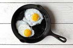 Two fried eggs in cast iron frying pan sprinkled with ground bla stock photo