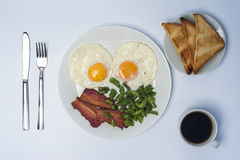 Two fried eggs with green beans and bacon on white plate, knife, fork, toasts and cup of coffee on light background. Stock Image