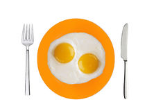 Two fried eggs on orange plate, knife and fork isolated on white Stock Photo