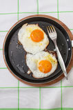 Two fried eggs in a pan and bread served at the table Stock Photos