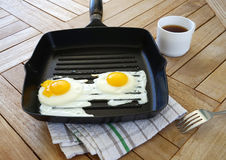 Two fried eggs on the pan and coffee on the table Royalty Free Stock Image