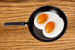 Two fried eggs on a pan on wooden table Stock Images
