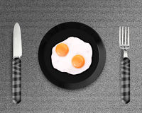 Two fried eggs on a Plate. Top view of two fried eggs on black Plate between silver knife and fork on gray background Royalty Free Stock Photography