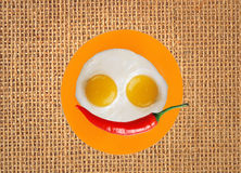 Two fried eggs and red hot chilly pepper on orange plate, knife Royalty Free Stock Photo