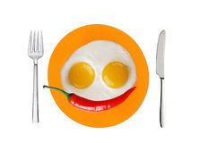 Two fried eggs and red hot chilly pepper on orange plate Stock Image