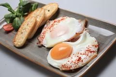 Two fried eggs with some bread and salad next to them.  royalty free stock images