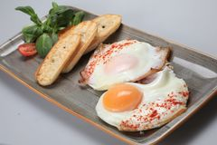 Two fried eggs with some bread and salad next to them.  royalty free stock image