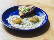Two fried eggs sunny side up egg on blue ceramic plate. On wooden table Stock Image