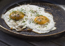 Two fried eggs sunny side up egg on old scratched pan. On wooden table Stock Image