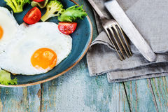 Two fried eggs and vegetables Stock Photos