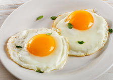 Two fried eggs on white plate for healthy breakfast Stock Image