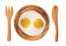 Two fried eggs on wooden plate, knife and fork isolated on white Royalty Free Stock Photos