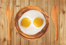 Two fried eggs on wooden plate, knife and fork on wooden table Royalty Free Stock Photos