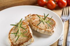 Fried pieces of pork chop with rosemary. Two fried pieces of pork chop with rosemary on plate and cherry tomatoes in background Stock Image