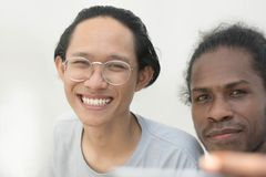 A two friend with diffrent ethnic taking selfie together and smiling, asian and black man selfie toghether stock photography