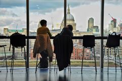 Two friend are having a coffee and talk with London skyline in t. He background Stock Photo