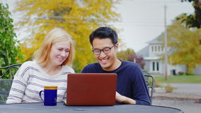 Two friend multiethnicity - Korean man and a Caucasian woman working together or watching a video on a laptop. stock footage