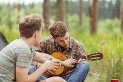 Two friend sitting in the tent, play the guitar and sing songs Royalty Free Stock Photo