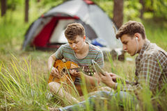 Two friend sitting in the tent, play the guitar and sing songs Royalty Free Stock Photography