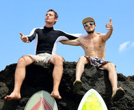 Two friend surfer sitting on a rock Royalty Free Stock Photography