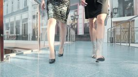 Two friend women walking cross legged wearing heels in shopping mall Royalty Free Stock Image