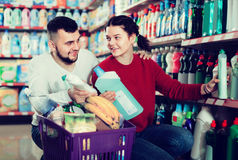 Two friendly adult people in good spirits selecting detergents i. Two friendly adult people in good spirits selecting detergents оn the shelves in the store Royalty Free Stock Image