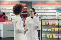 Two friendly colleagues talking while working together as pharmacists stock image
