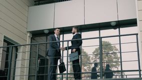 Two friendly coworkers meeting outdoors and shaking hands firmly. To greet each other in the morning stock video